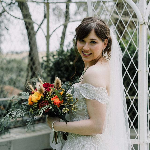 wedding videography melbourne portfolio of boho bride holding rustic flower bouquet at Overnewton Castle