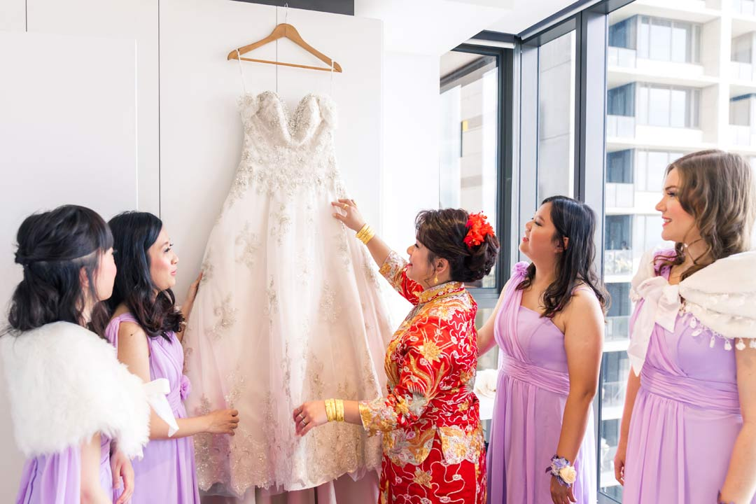 bridesmaids help bride hang her white wedding dress in Melbourne apartment bedroom