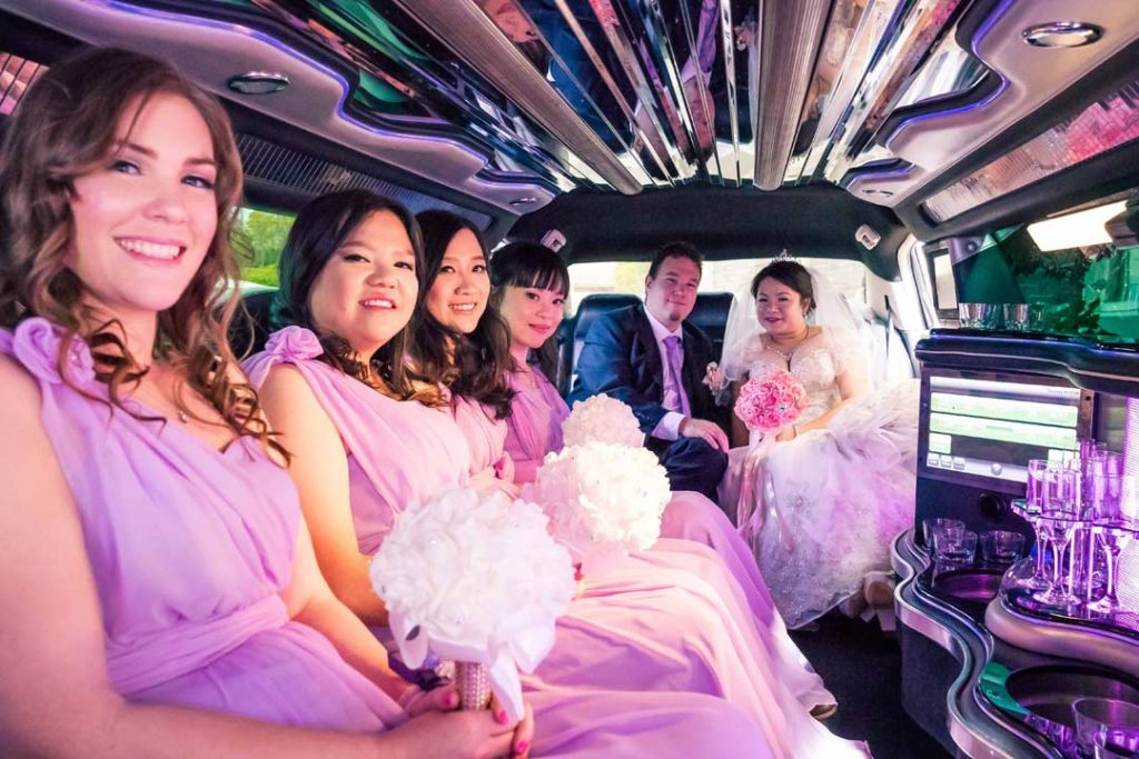 bridal party drinking bubbly wine inside Amazine Limousines to celebrate wedding day at Merrimu Receptions