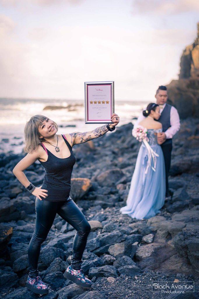Melbourne female photographer holding a 5 star award frame by Easy Weddings photobombed an engaged couple posing on Mornington pebble beach for a photo