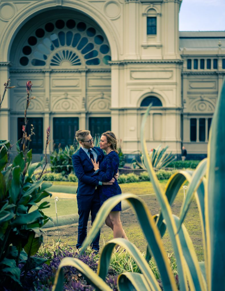 Melbourne engagement photography showing couple hug each other outside Royal Melbourne exhibition centre artistically composed