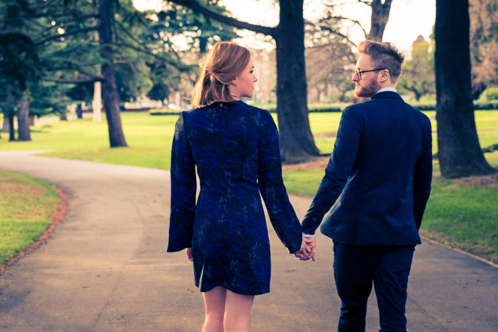 Melbourne couple holding hands in their blue attire walking in Melbourne park for pre wedding photo by Black Avenue Productions