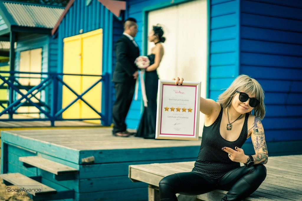 Melbourne based female wedding photographer holding her Easy Weddings 5 stars supplier award frame in front of engaged couple in a black dress posing on Mornington beach house