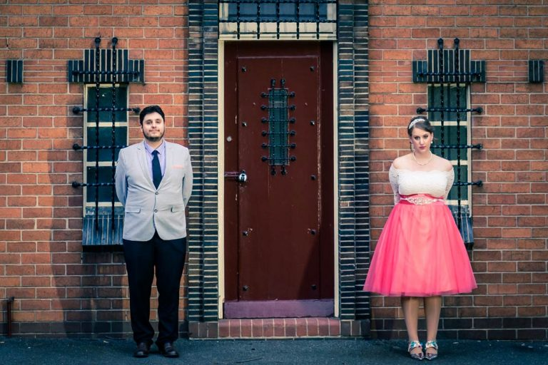 funny couple standing still for their unique style wedding photography in Melbourne taken by Black Avenue Productions