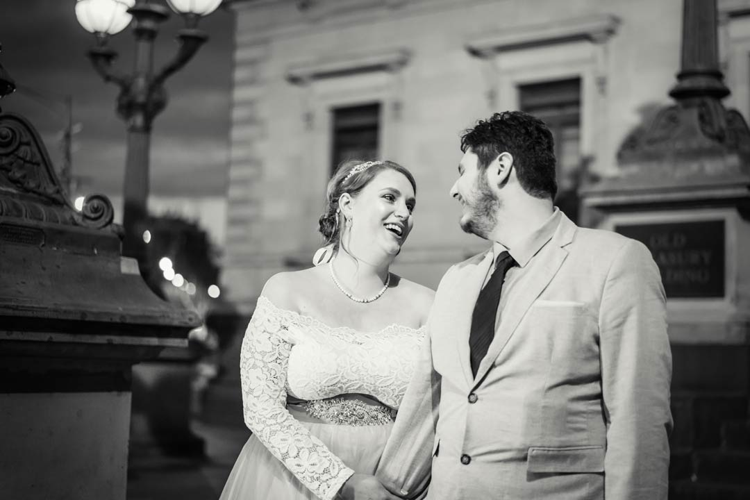 married couple happily laughing outside Victorian Marriage Registry Old treasure building by sunset by Black Avenue Productions