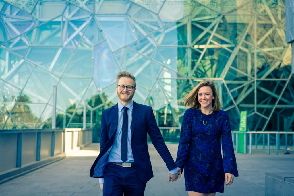 ACMI Melbourne engagement photo with Melbourne couple holding hand smiling and walking together in her blue dress