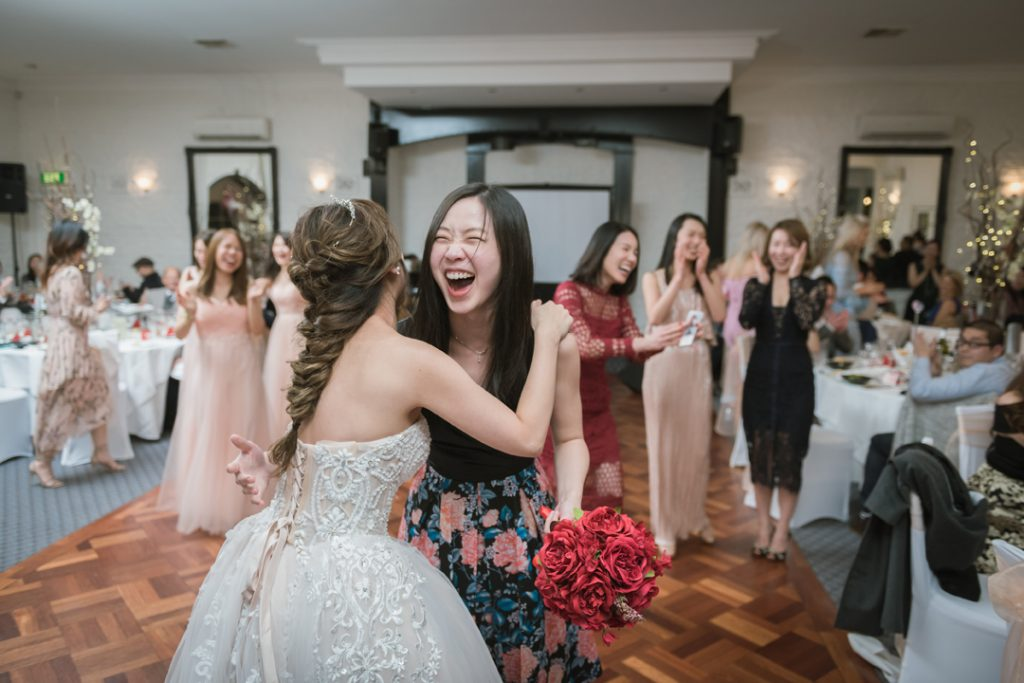 bride hugged guest who received flower bouquet moment capture by Black Avenue Productions at Bram Leigh Wedding