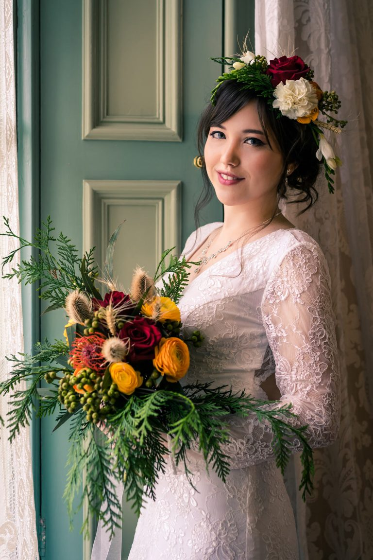 beautiful bride wearing woodland theme flower crown and vintage lace boho bridal gown holding a big bunch of forest Aussie flower bouquet standing in Overnewton Castle captured by wedding photographers Melbourne Black Avenue Productions