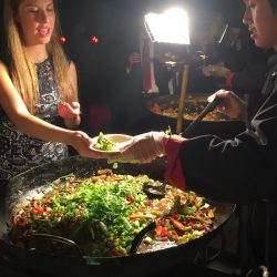 Flying Woks staff serving wedding paella to guest at night