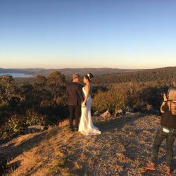 Melbourne wedding photographer shooting bride and groom on top of hilltop cliff on Reeds lookout Australia in sunset