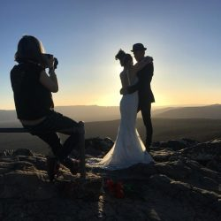 proposal photography behind the scene image showing Melbourne wedding photographer photographing married couple under sunset light on stunning hill top cliff in the Grampians Australia