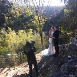 professional travel photographer in Melbourne photographing married couple by McKenzie Falls in the Grampians behind the scene image by The Black Avenue Productions