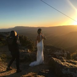 amazing award winning photo of stunning bride in her lace wedding gown standing on mountain top at Reeds look out at The Grampians captured by Black Avenue Productions