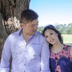happy couple resting under a tree capture by wedding photographers Melbourne