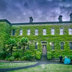 fine art style pre wedding photography at Victoria Barracks artistically edited to have purple stormy weather with a couple walking pass by