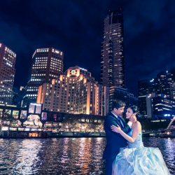 Night time wedding photo in front of Yarra River overlooking Langham Hotel in Melbourne with bride and groom dancing in the moonlight