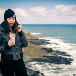 outdoor style girl standing on hilltop cliff overlooking the ocean and waves for her lifestyle photo shoot captured by Melbourne wedding photographers Black Avenue Productions