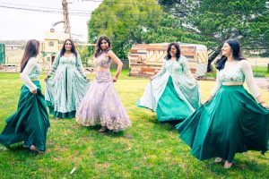 five bridesmaids and bride dancing and circling with their ballgown dresses on a field at Baxter Barn Melbourne captured by Black Avenue Productions