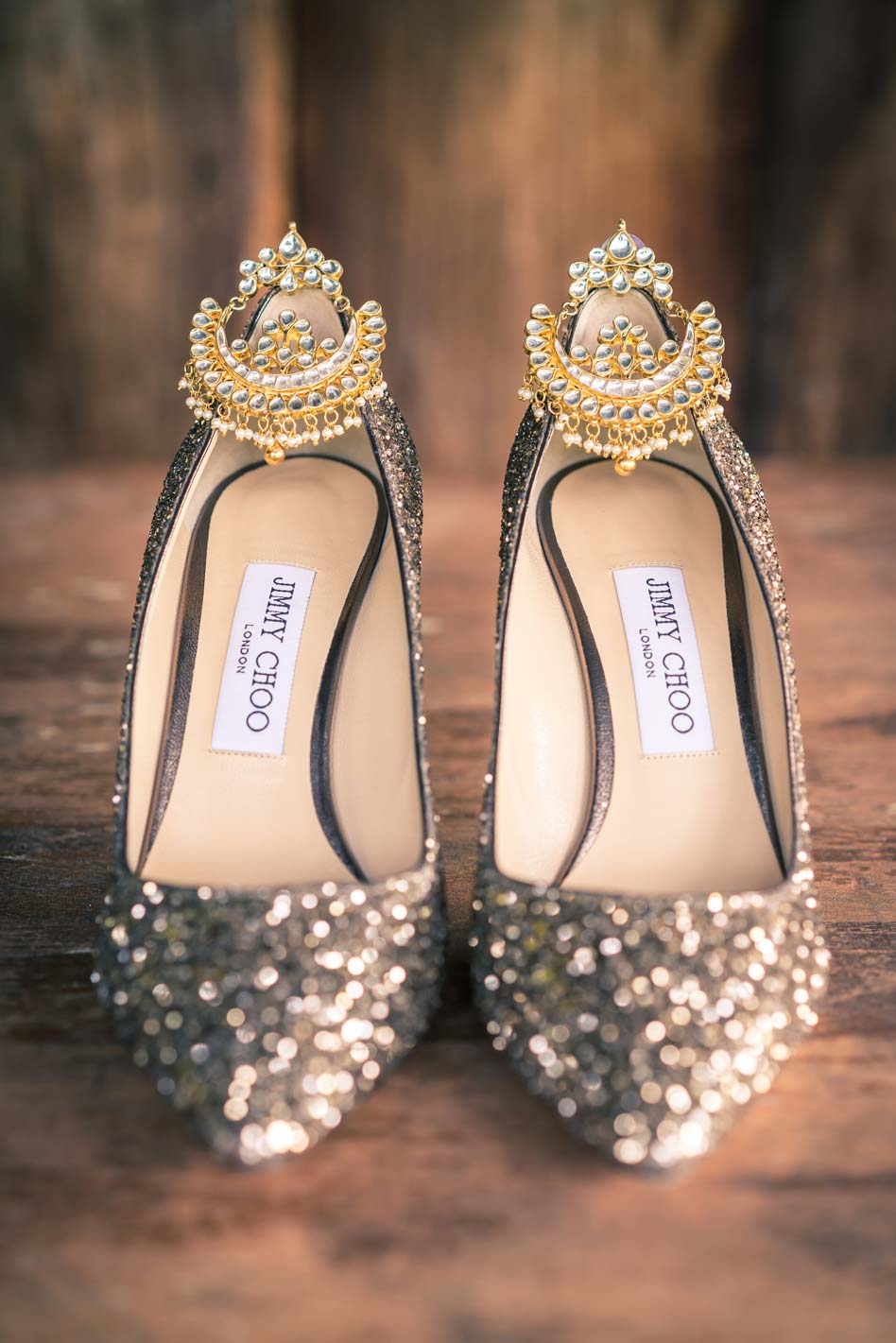 artistic wedding photography showing golden earrings hanging on sparkling Jimmy Choo Cinderella wedding shoes on wooden table at Baxter Barn by Black Avenue Productions