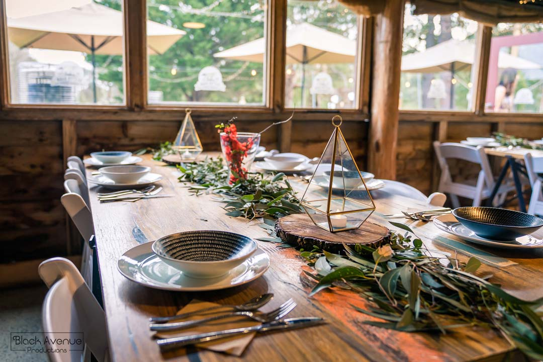 rustic greenery wedding inspiration image of Baxter Barn receptions table setting with organic plants and flowers in natural sun light