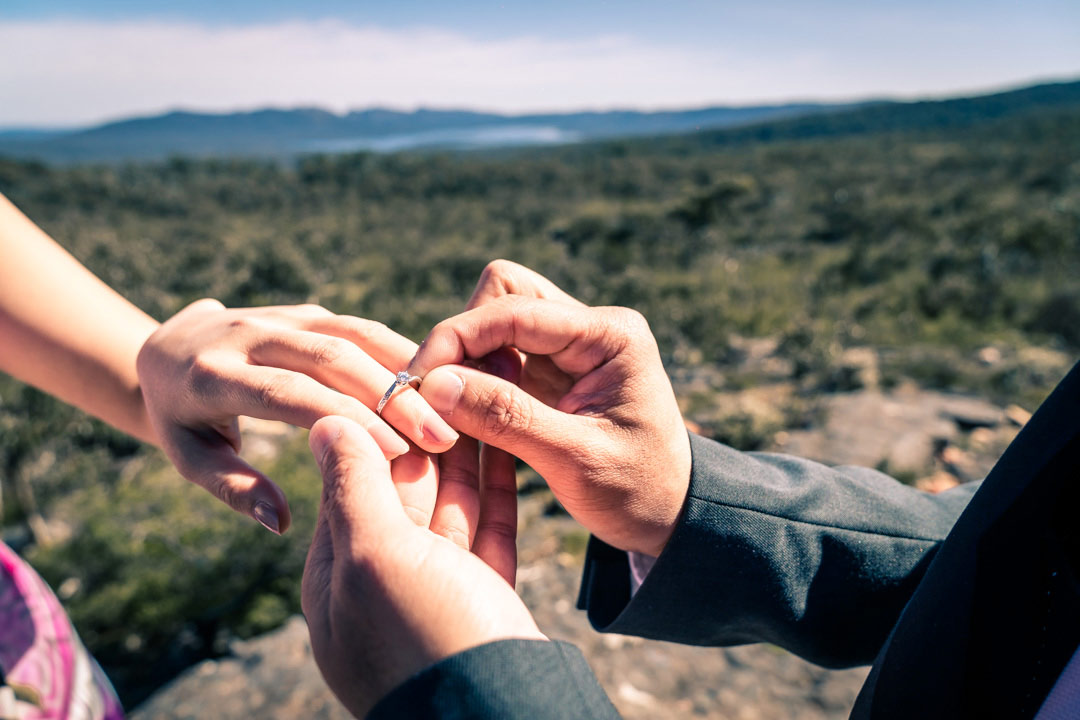 proposal photography showing boyfriend putting engagement ring to girlfriend middle finger candid photo