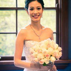 stunning happy bride holding white peach rose wedding flower bouquet by the window at Marybrooke Manor wedding reception venue