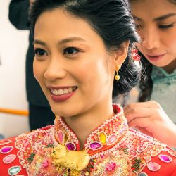 Hong Kong bride wearing red and gold Chinese wedding gown getting ready for Tea ceremony in Melbourne Australia