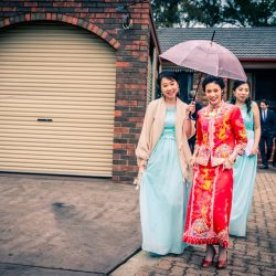 Hong Kong bride wearing red and gold bridal gown with bridesmaids walking towards limo car