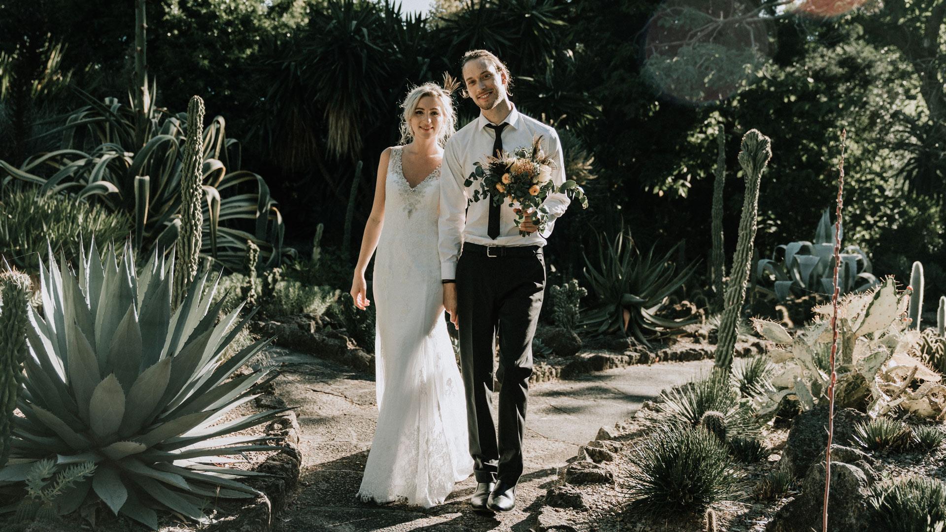 wedding photographers Melbourne image of boho bride and groom walking across Royal Botanical Gardens