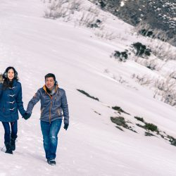 engaged couple having a walk on snow mountain for their pre wedding photo