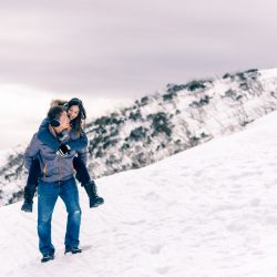 boyfriend carry his girlfriend picky back style on snow mountain at Falls Creek Australia