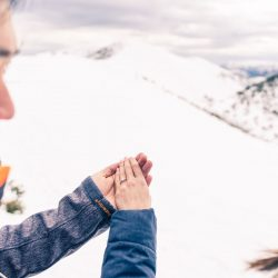 romantic engagement photo idea showing engagement ring in a snow mountain