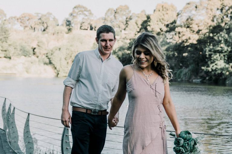 Australian engaged couple holding hands walking around a lake in Berwick Botanical Gardens candid shot by Black Avenue Productions