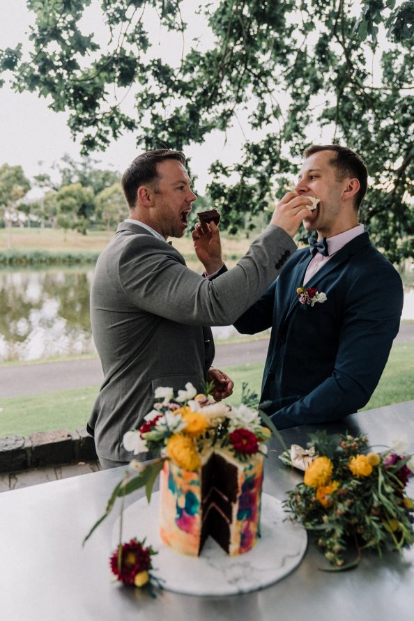 Melbourne gay couple feed each other rainbow wedding cake in Royal Botanical Gardens