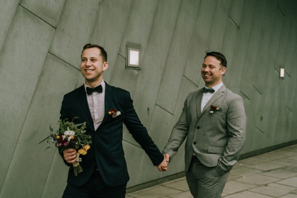 happily married gay husband and husband holding hand going to their reception