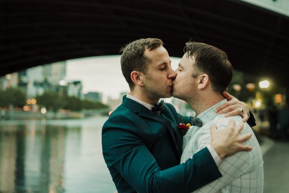 in love gay couple kissing passionately under sunset by Southbank river in Melbourne Australia