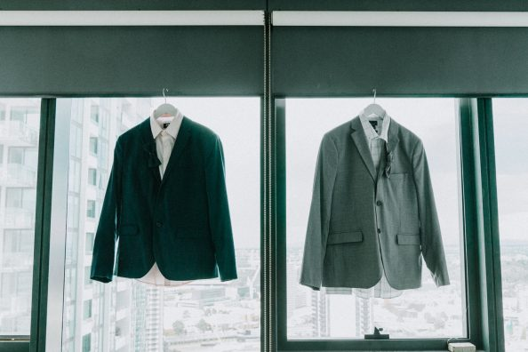 two wedding suits hanging together in a City Road Southbank apartment for a gay wedding