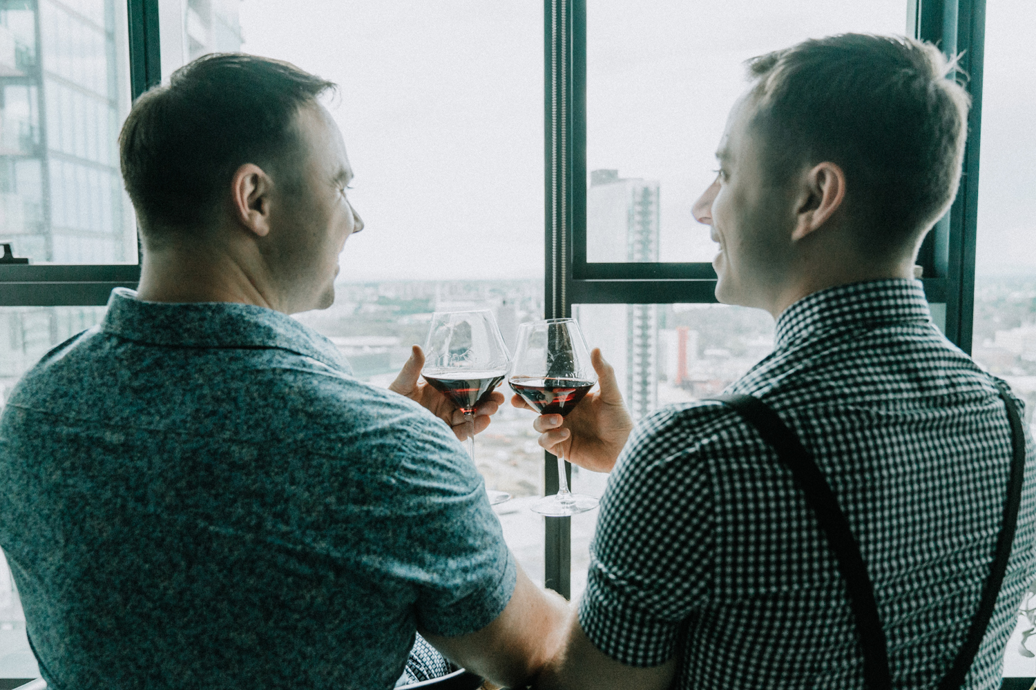 same sex gay couple cheers red wine at City Road Southbank apartment balcony for love