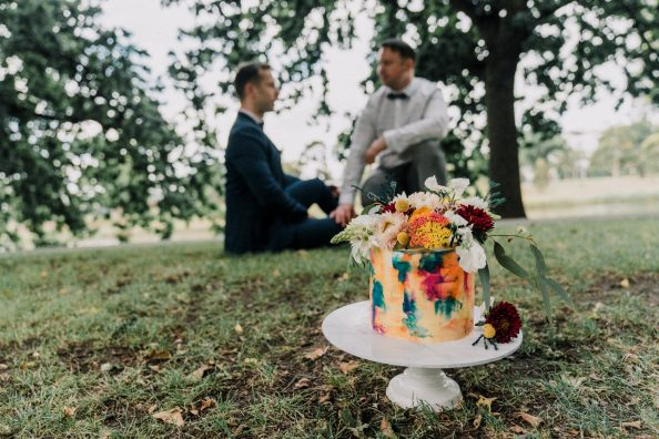 gay engaged couple enjoying time in the Botanical Gardens with rainbow cake image by Melbourne wedding photographers Black Avenue Productions