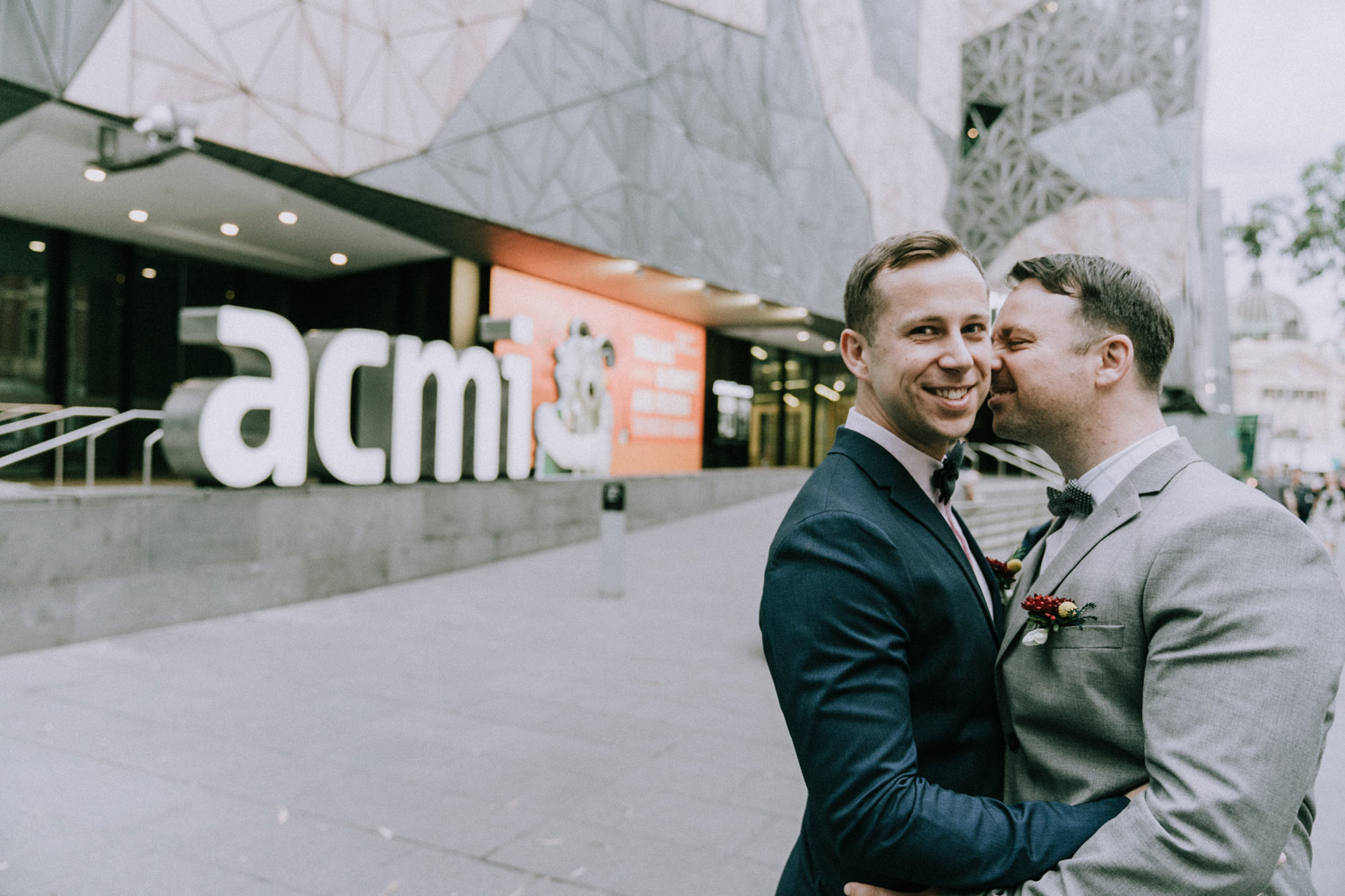 gay boyfriends kissing each other outside ACMI Melbourne for wedding photo