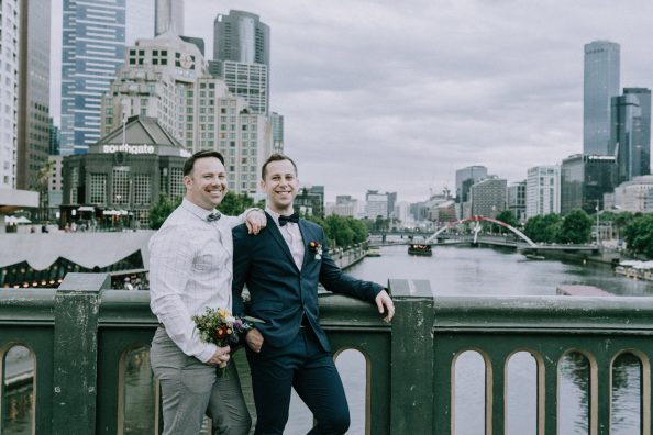 same sex couple posing on Princess bridge for Melbourne gay wedding photo