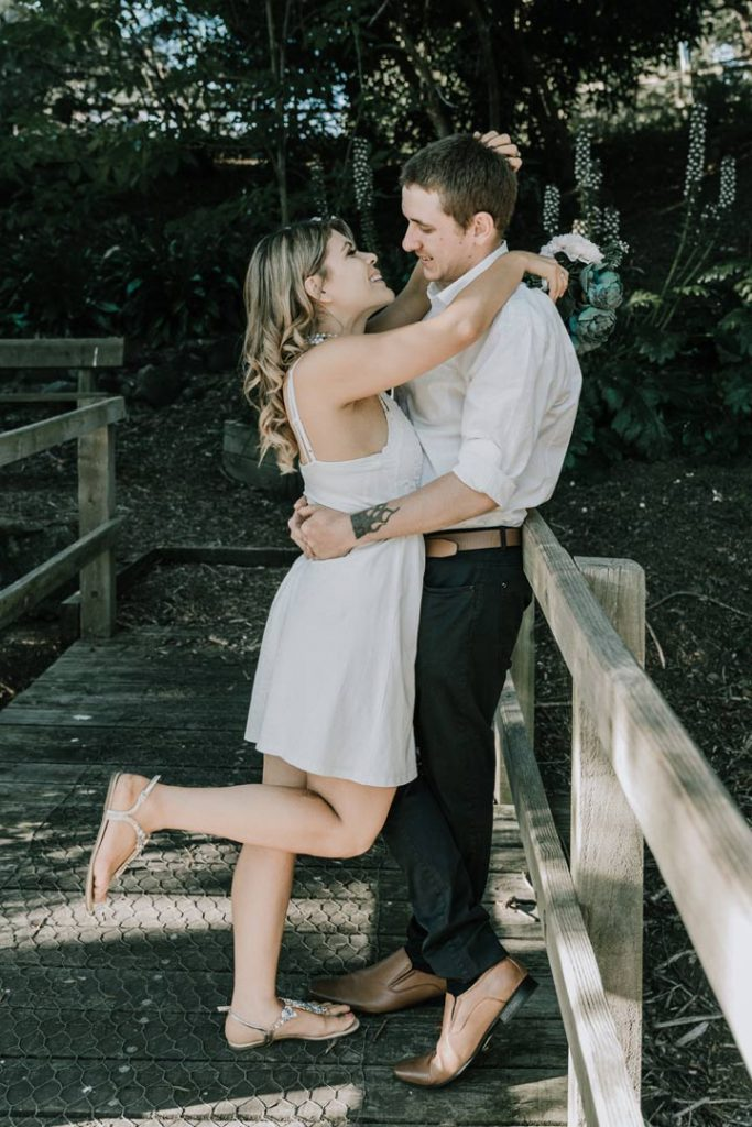 engagement photo of happy couple hugging in white attire captured by Melbourne wedding photographers Black Avenue Productions at Berwick Botanical Gardens