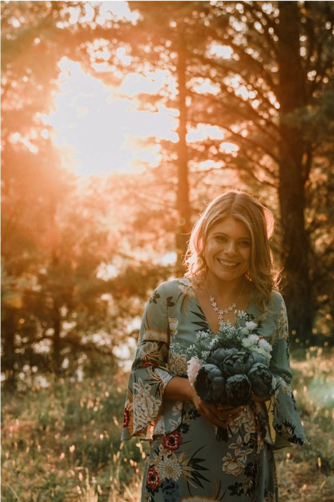 Pretty blonde hair Australian girl holding bridal bouquet under magic hour sunset backlit wedding photo by Black Avenue Productions