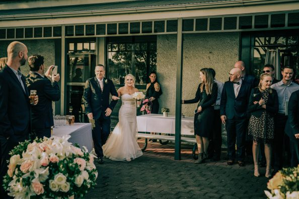 father walking daughter down aisle at Yarra river wedding venue ceremony action shot