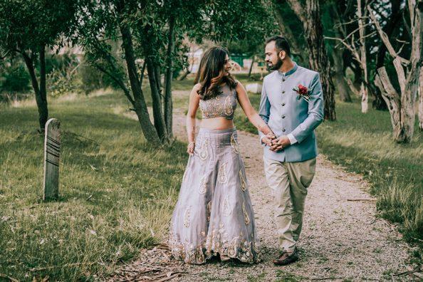 Indian bride groom walking across the woods rustic barn wedding photo