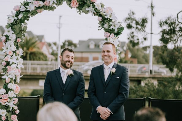 excited groom and groomsmen waiting for bride at wedding ceremony