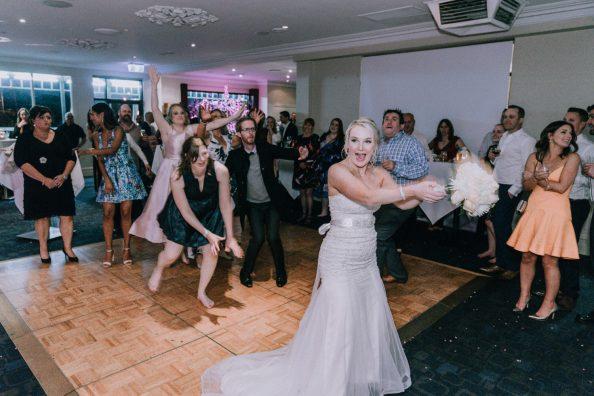 bride throw flower bouquet at wedding reception in Melbourne