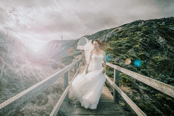 stunning bridal portrait showing bride walking down the bridge at backlit in Cape Shank