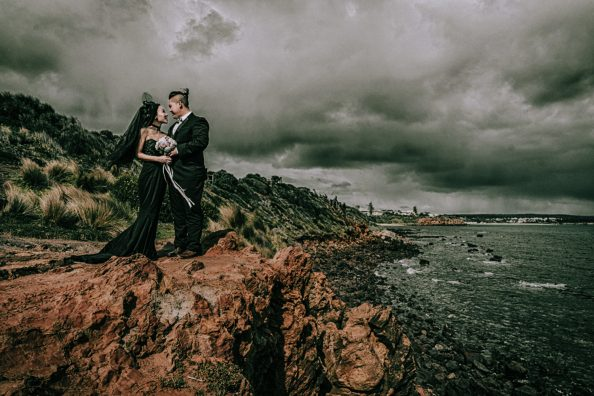 offbeat bride in black bridal gown pose for artistic wedding photo by the hilltop