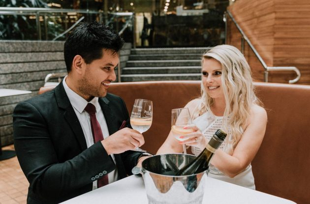 couple cheers to champagne during pre wedding photo shoot at popular Melbourne wedding location Kino Cinema